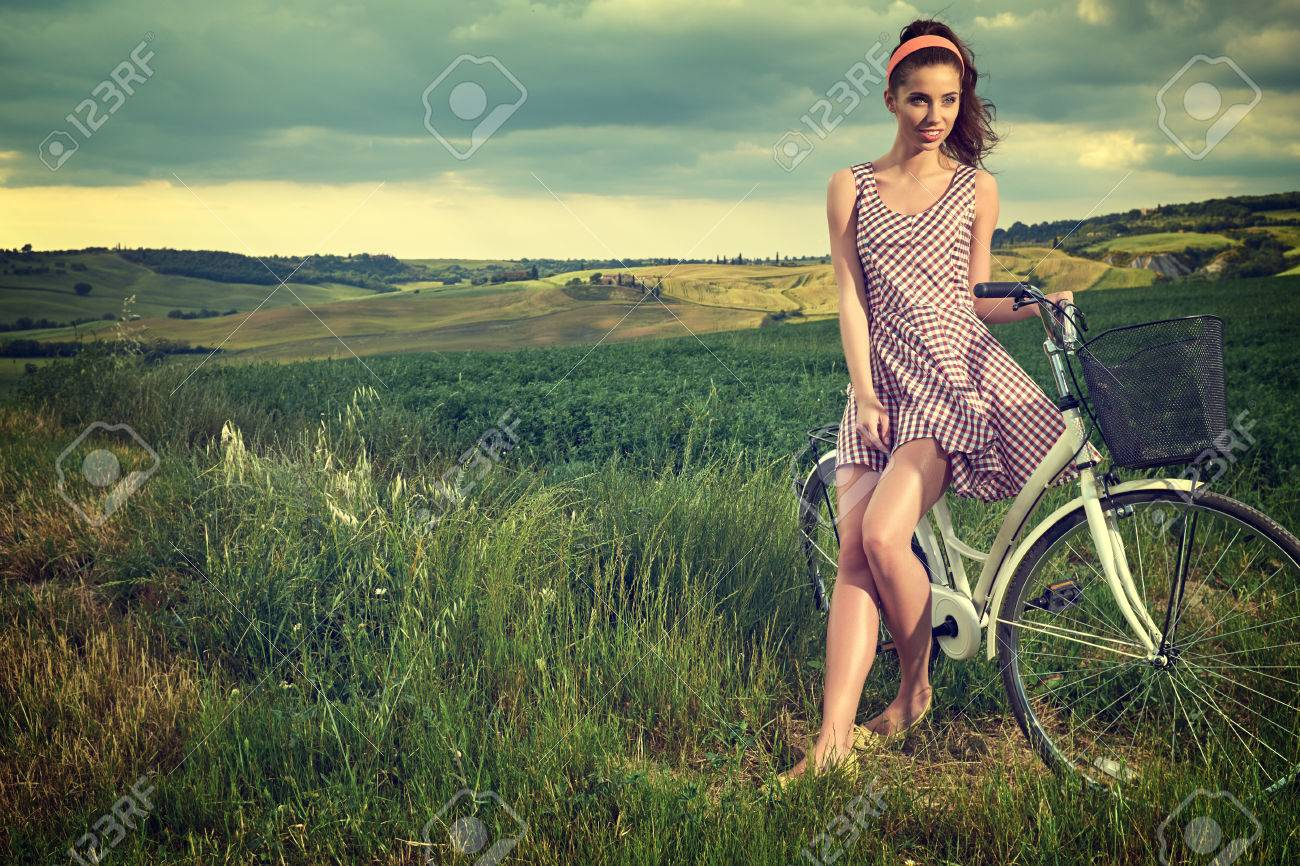 beautiful girl with vintage bike outdoor, summer Tuscany time - 57997739