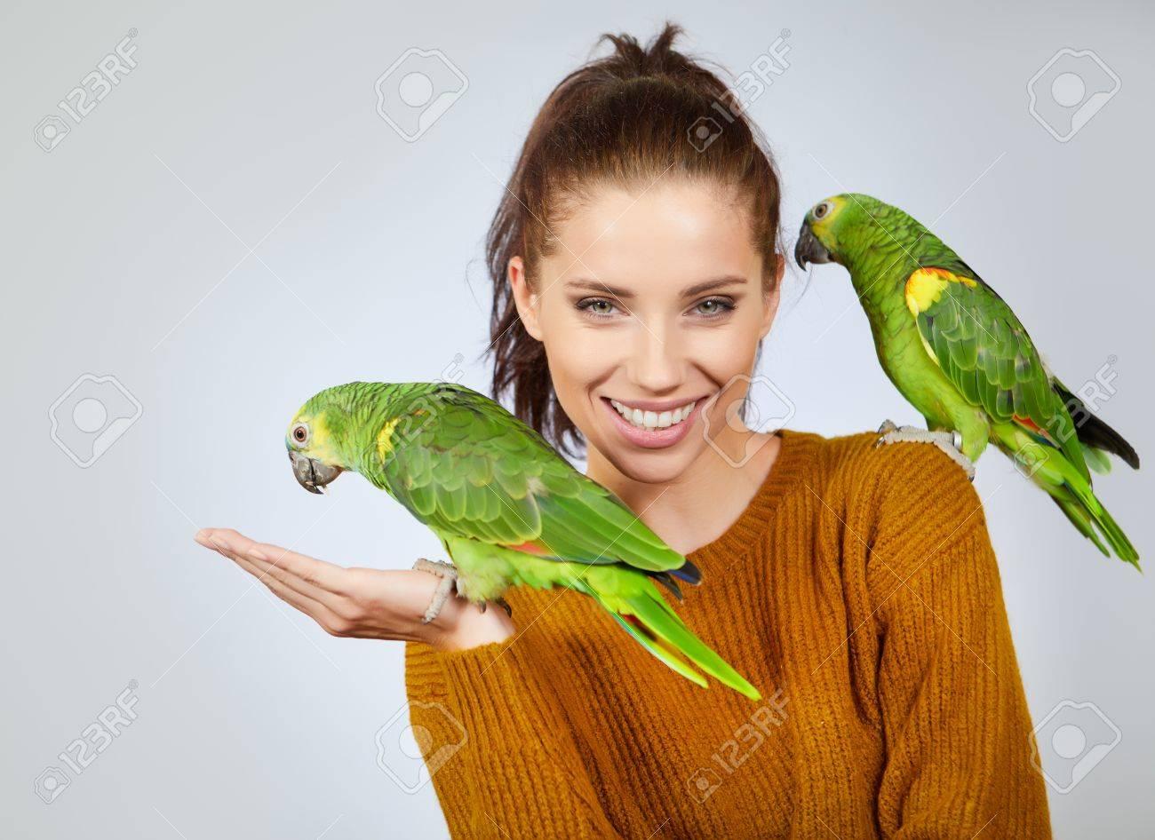 Two bird, cute parrots, sit on woman. Studio shoot - 83665858
