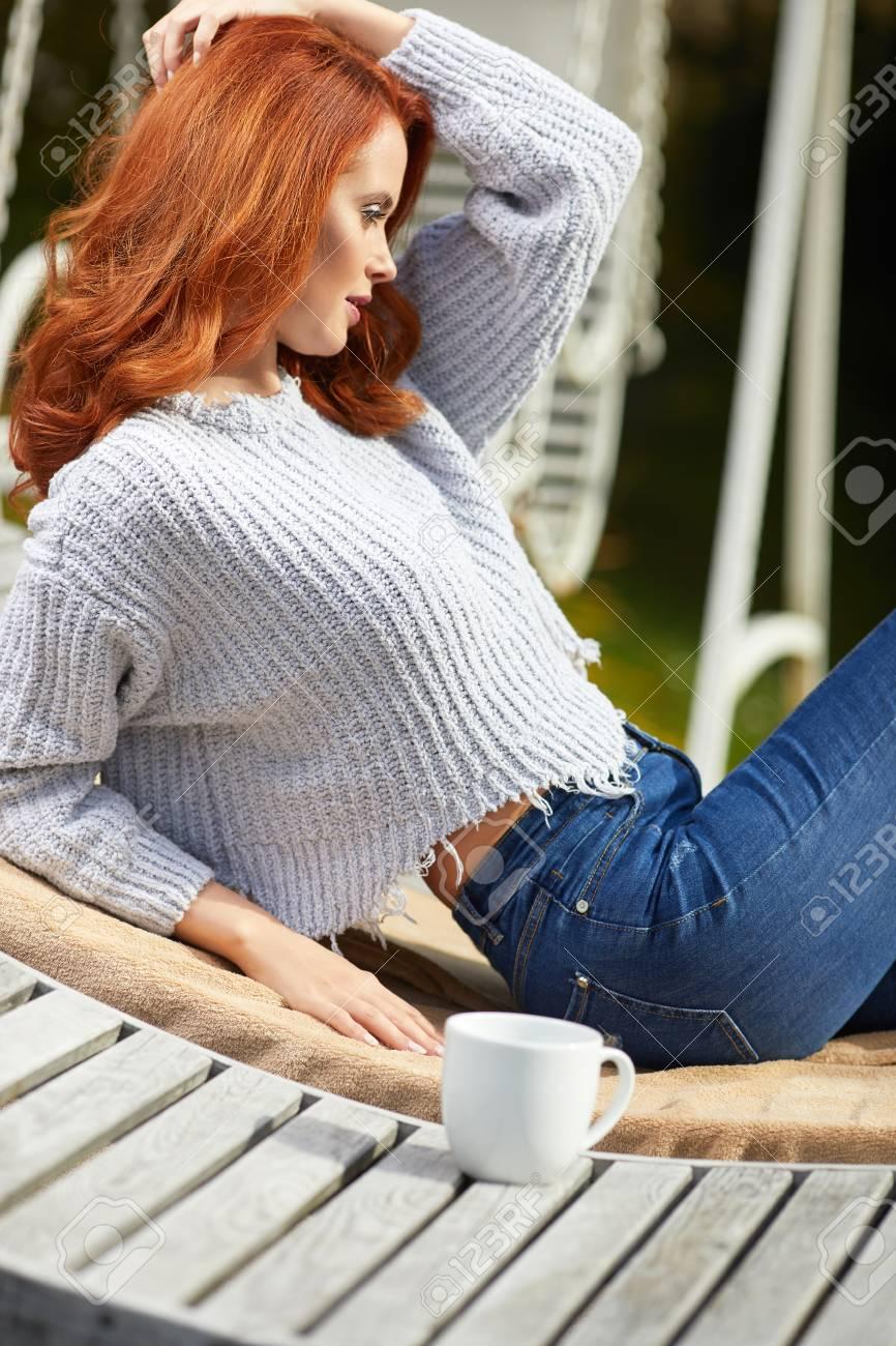 Mujer Relajante En Una Terraza De Madera En La Mañana Modelo Femenino Con Lredhaired