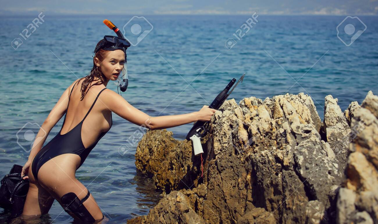 woman with fins and crossbow is preparing to hunt for fish - 128073629