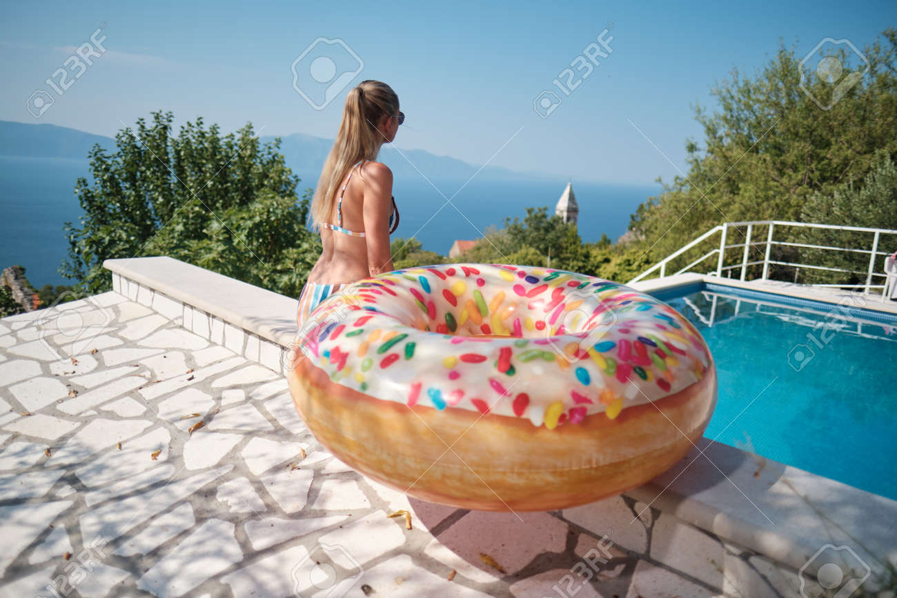Holiday resort in Croatia. Woman next to swimming pool with sea view. Vacation relax. Sea with mountains at background - 162108073