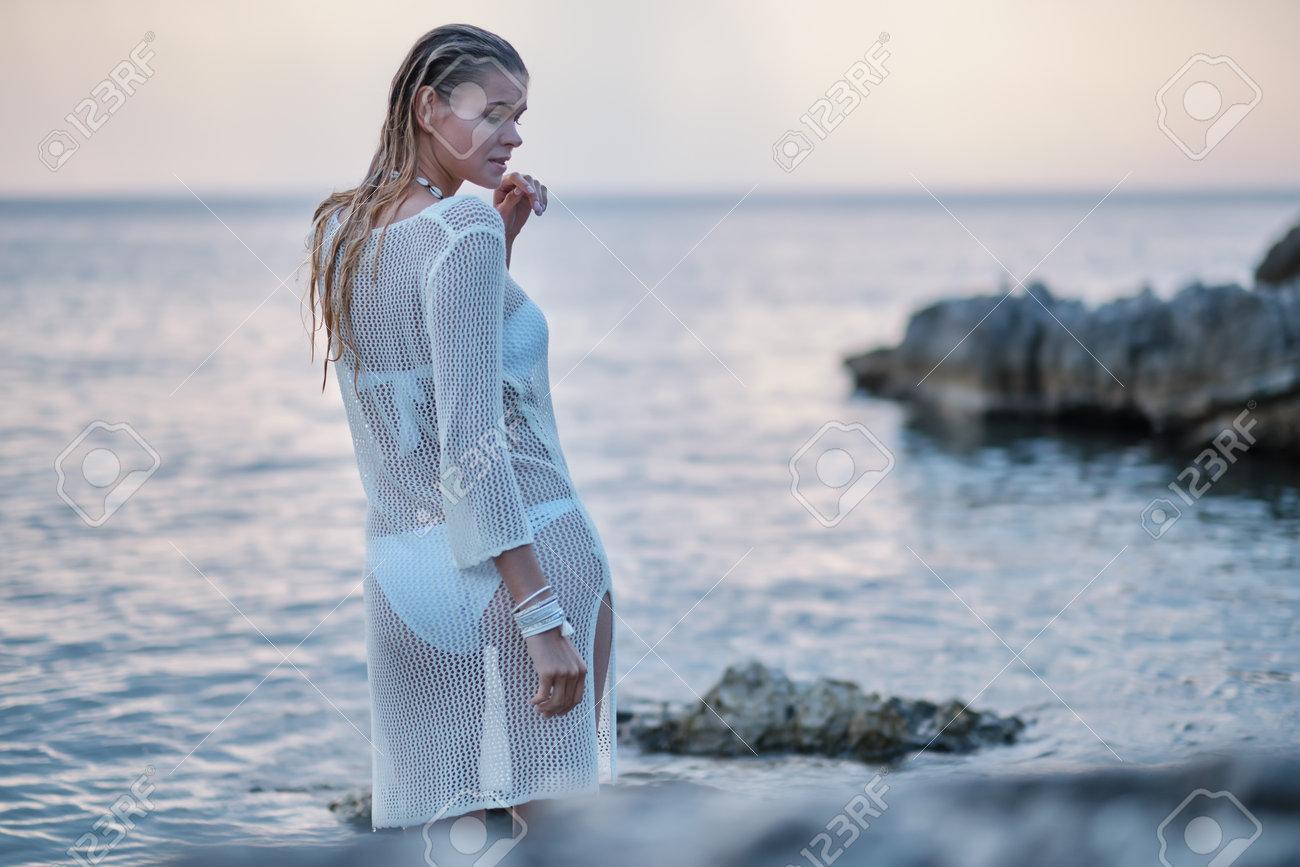 A woman on a rocky beach in Croatia. - 162108027