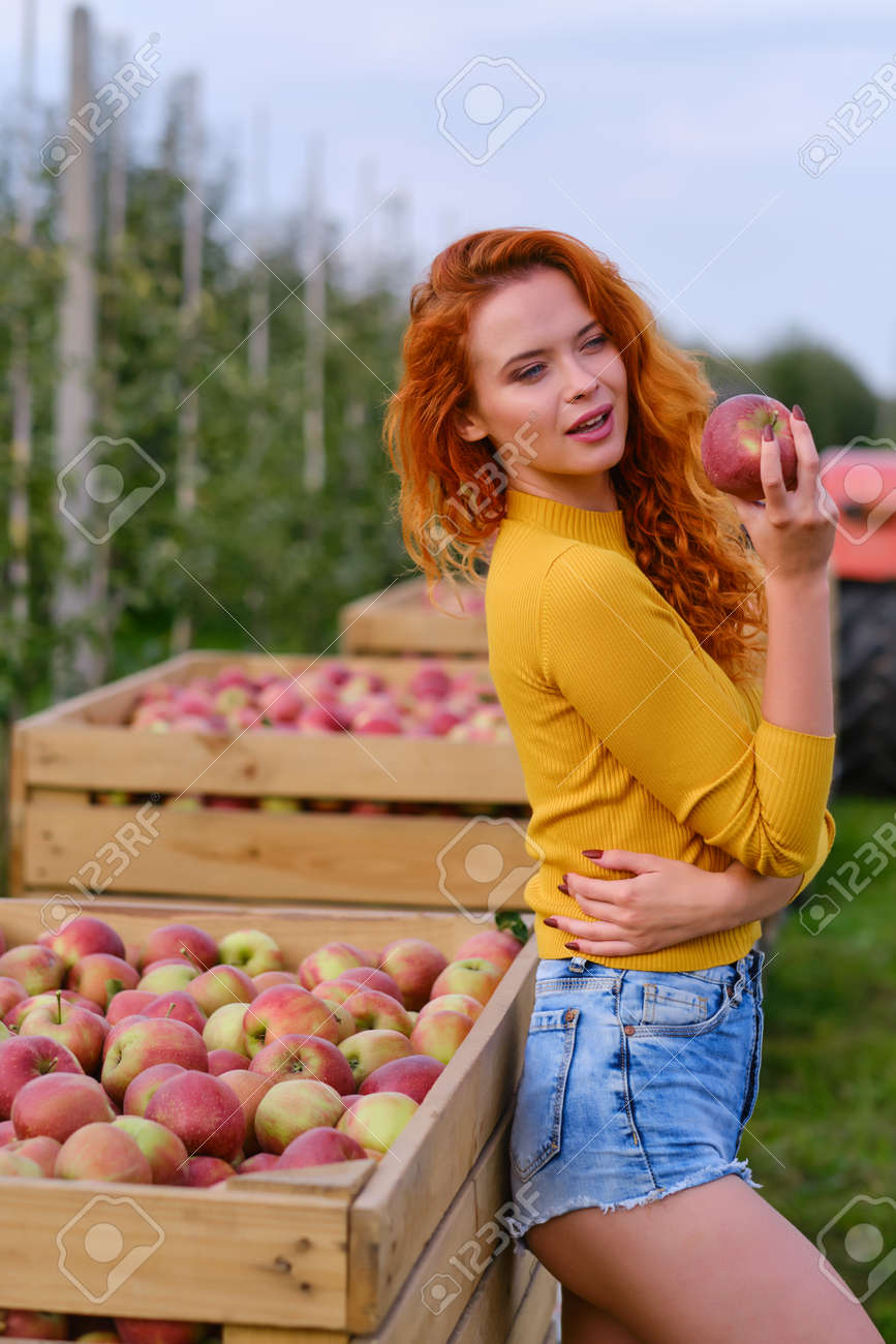 young woman cute blond girl smiling among red apples sun light flares of rays looking at camera on summer outdoor copy space background - 163057247