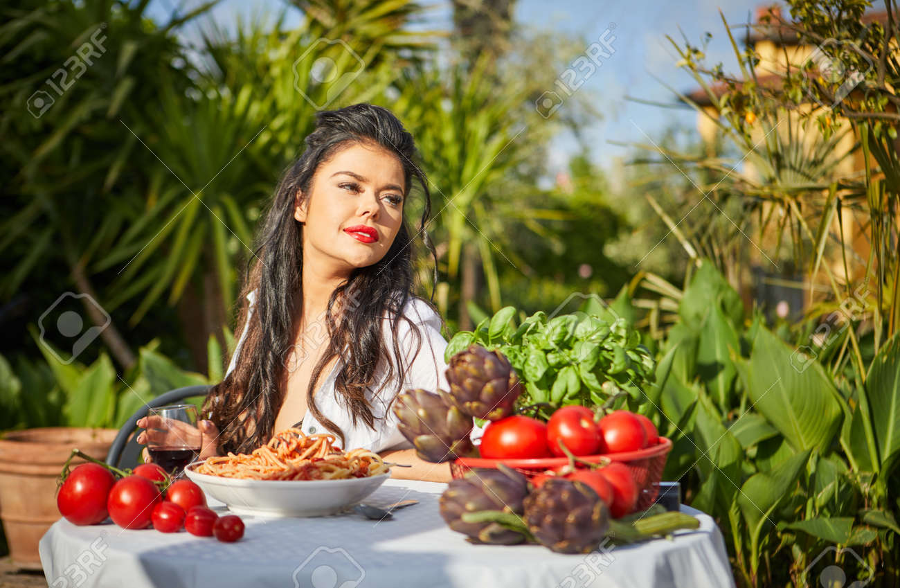 country life. An Italian woman eats dinner and pasta in her home garden - 163563079
