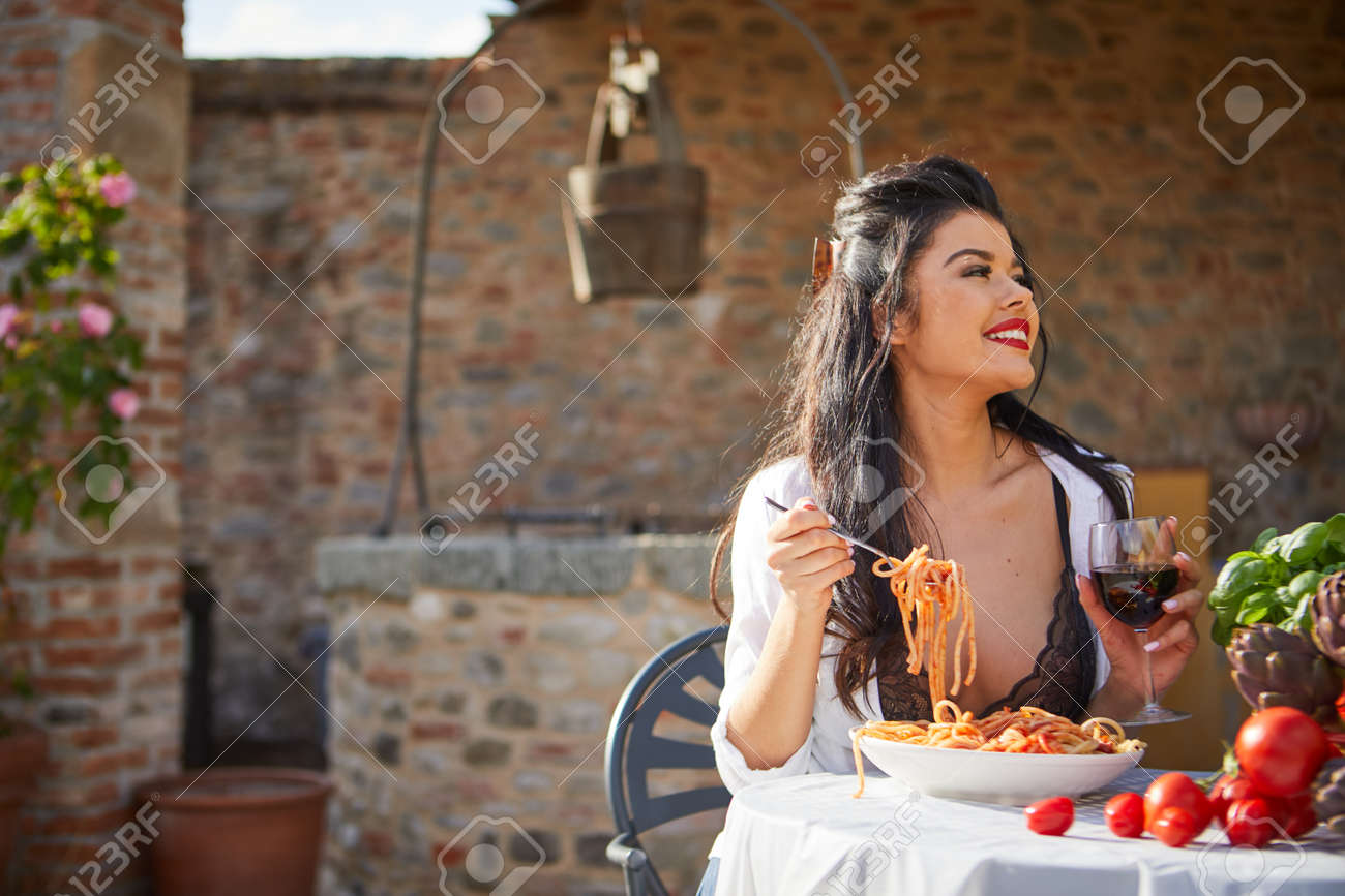 country life. An Italian woman eats dinner and pasta in her home garden - 163563080
