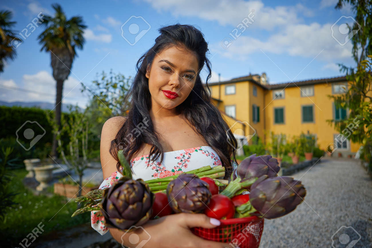 Woman holding basket of vegetables outdoors at her garden. italian life style - 166052450