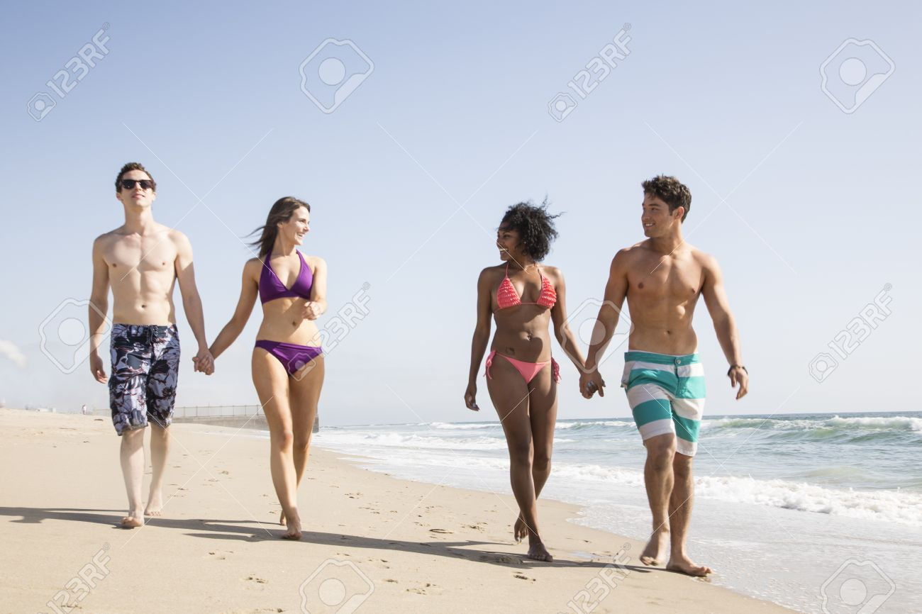 Two Young Couples Walking Along The Beach Stock Photo Picture And