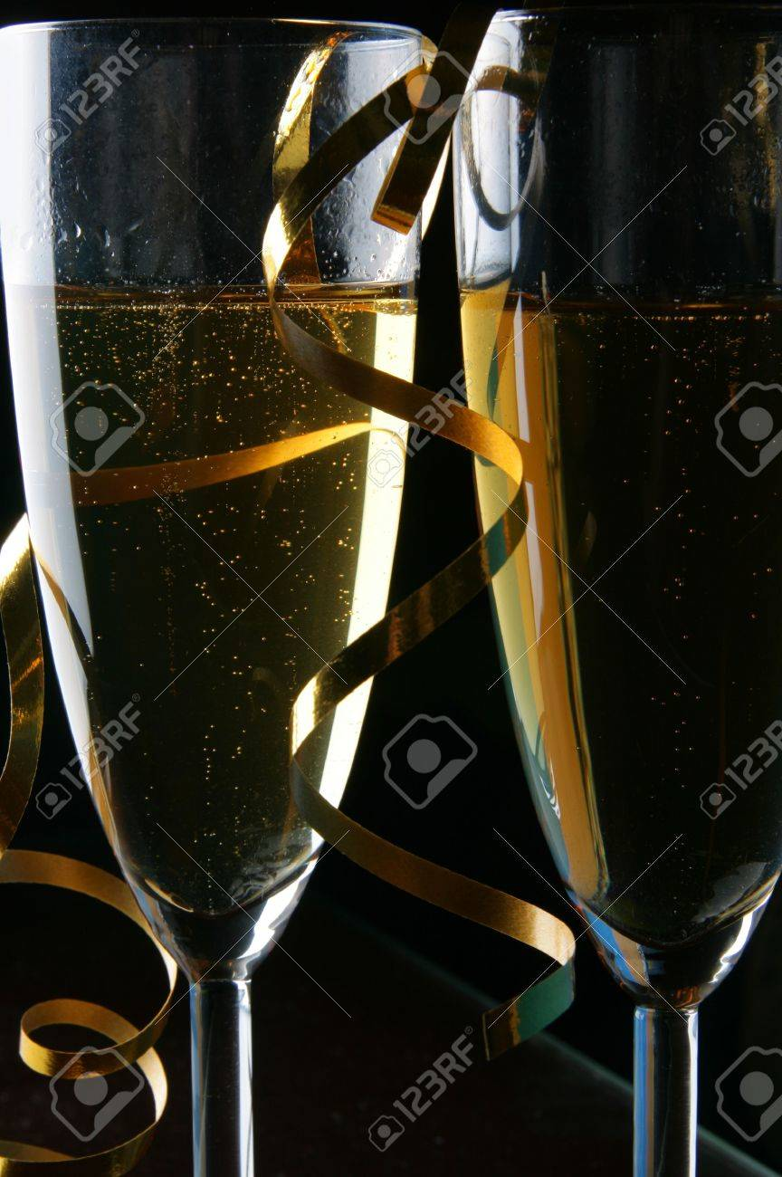 Two glasses of champagne and gold streamer over black background Stock Photo - 3233759