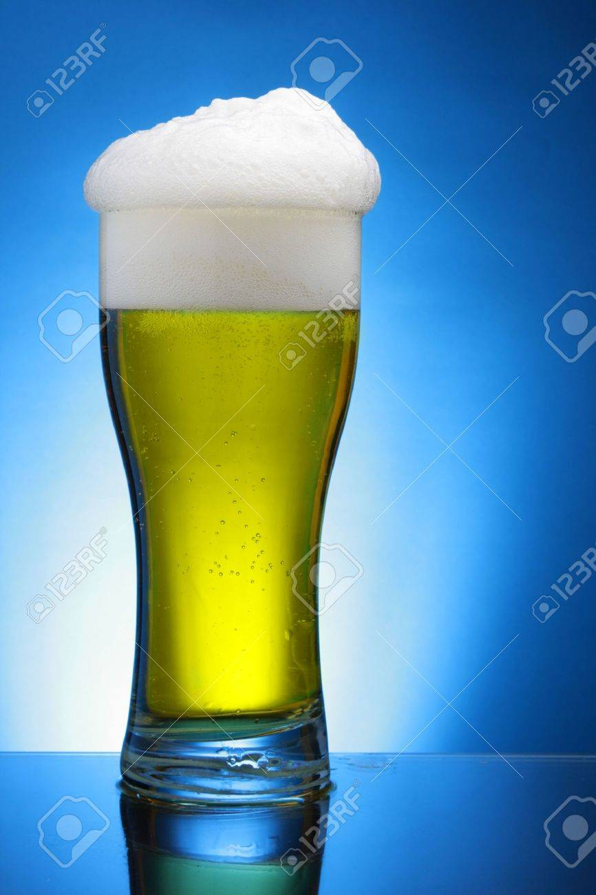 Glass of beer close-up with froth over blue background Stock Photo - 3233738