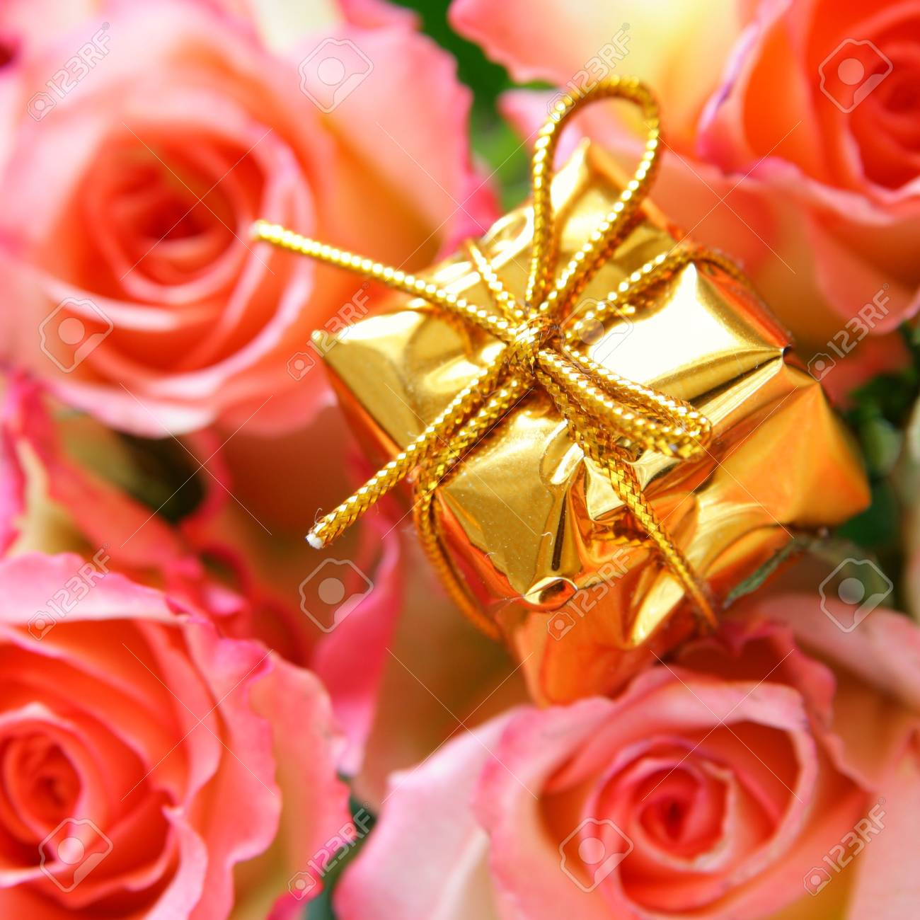 Gold box with gift and rosebuds in the background out of focus Stock Photo - 3865455