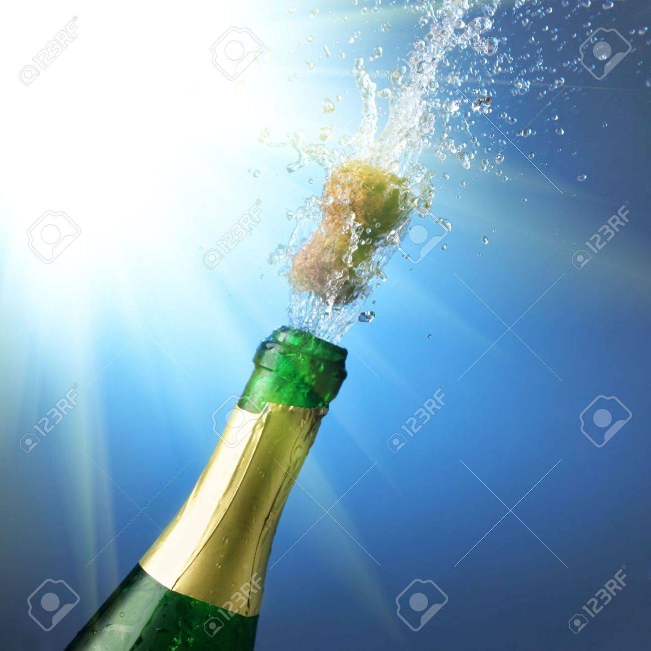 Bottle of champagne with splashes over blue background Stock Photo - 3865388