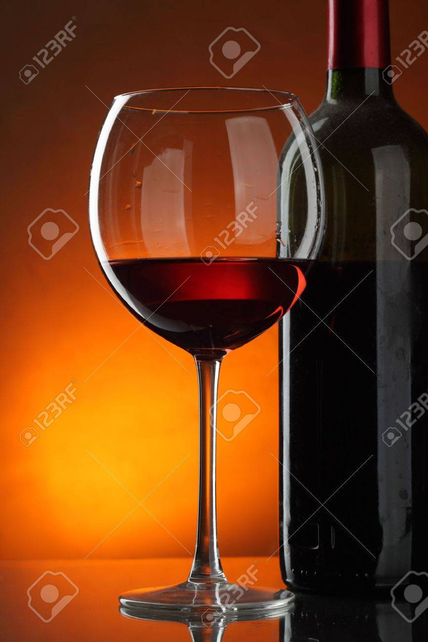 Glass and bottle of red wine over dark red background Stock Photo - 5949965