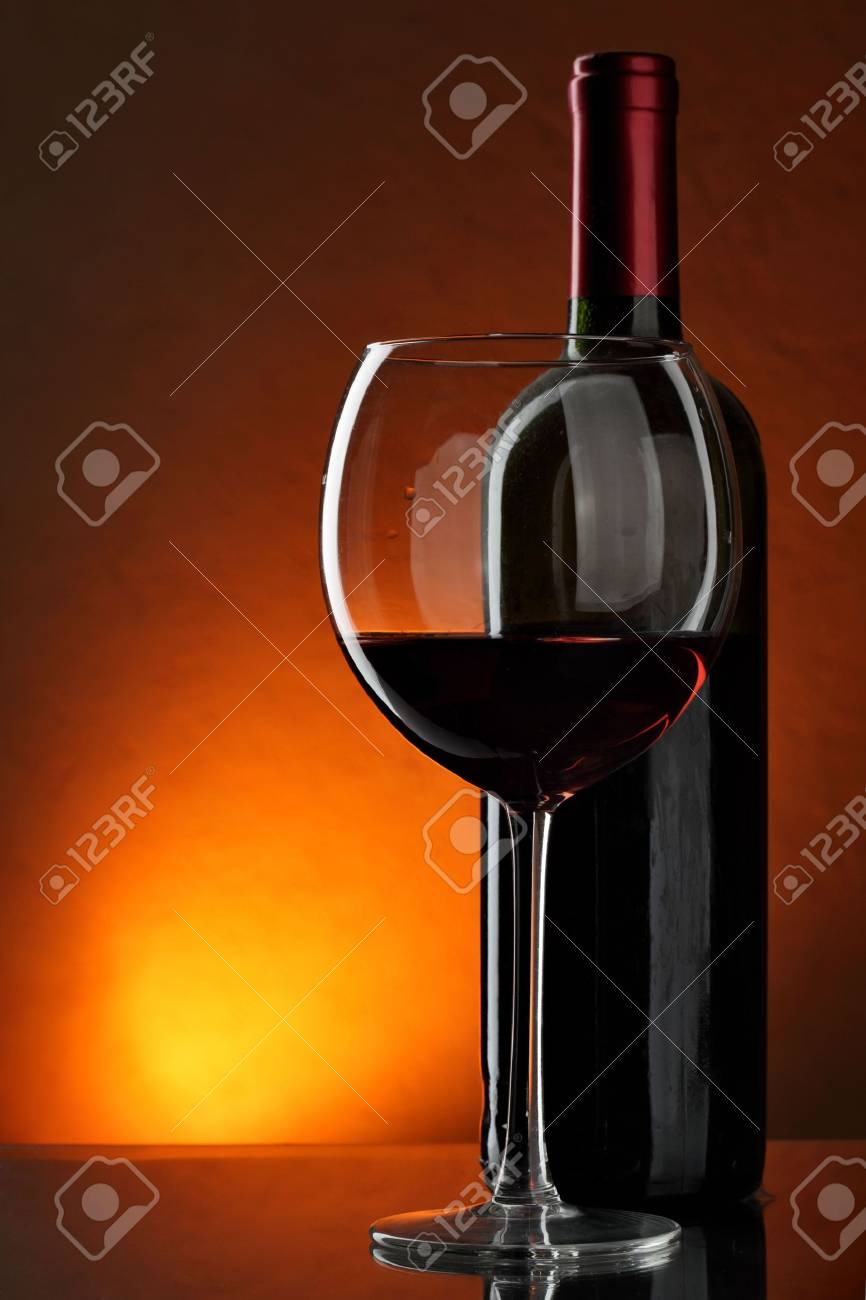 Glass and bottle of red wine over red background Stock Photo - 6458706