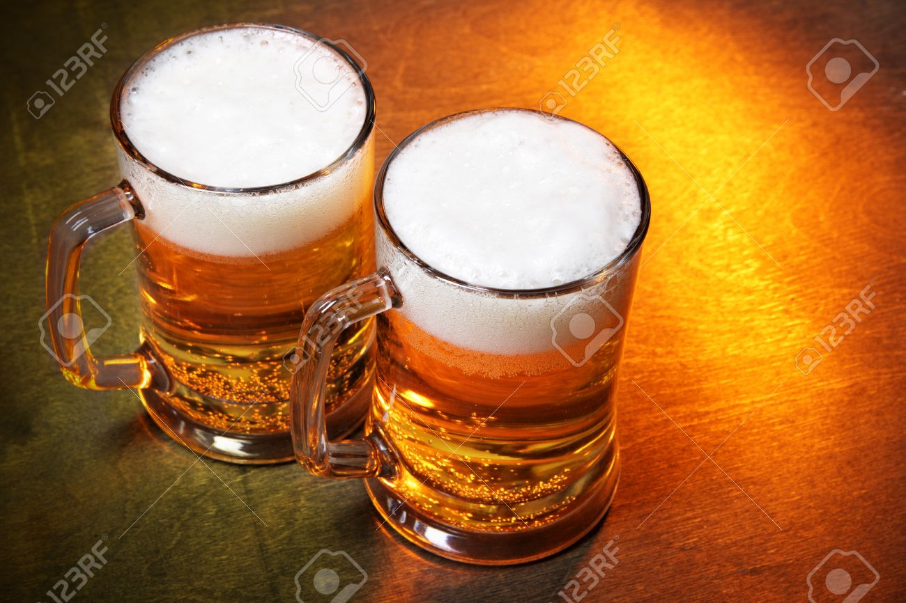 beer mugs close up on wooden table stock photo