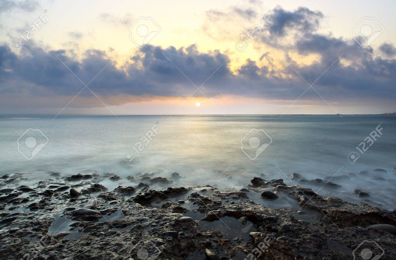 Beautiful sundown at rocky beach. Water in motion blur. Stock Photo - 8243119