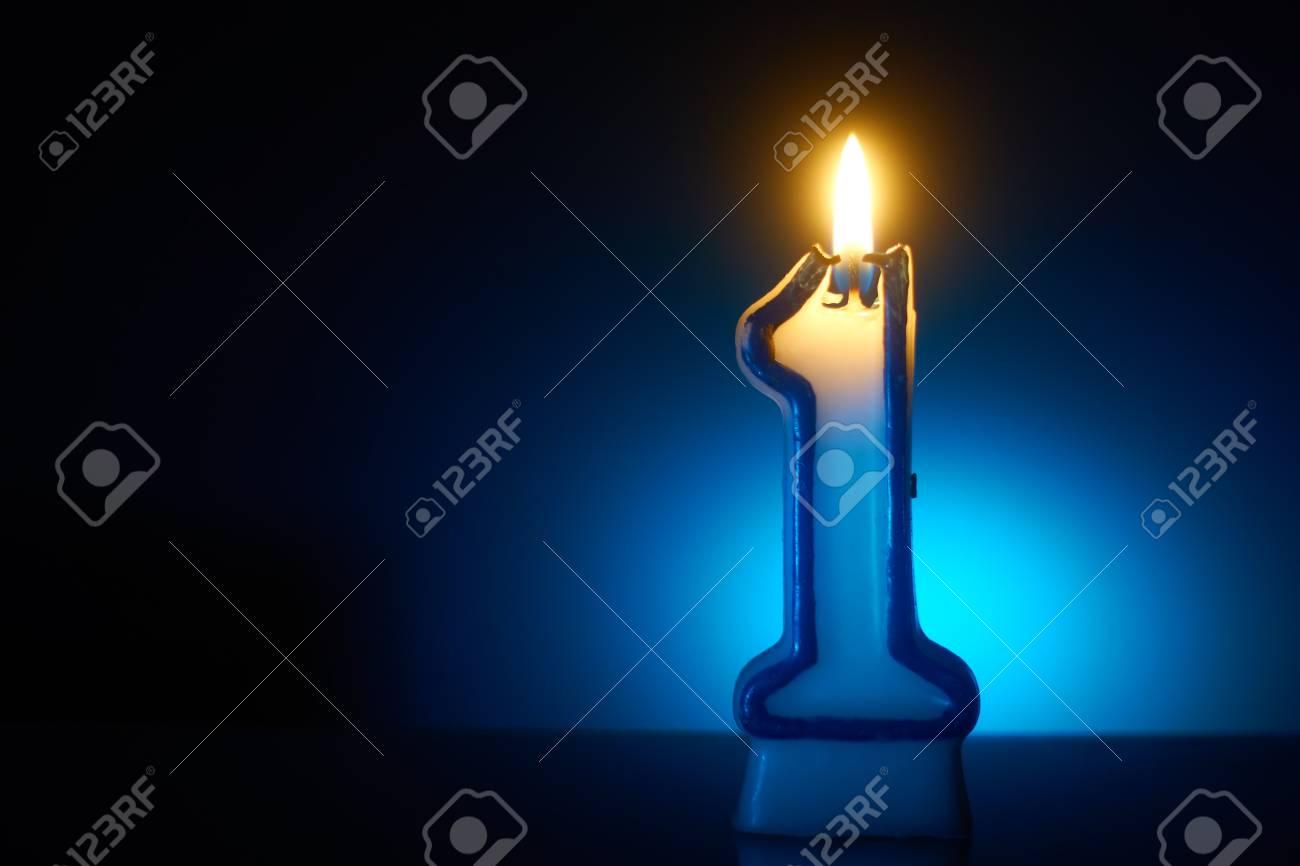 Number One - Burning birthday candle on blue background - 99498955