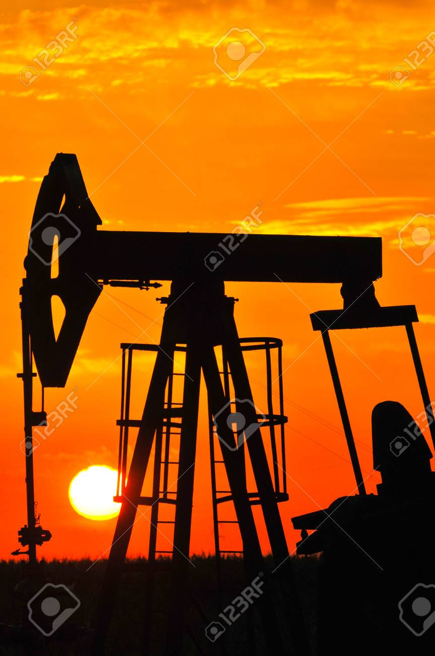 An oil pump jack is silhouetted by the setting sun Stock Photo - 14458898