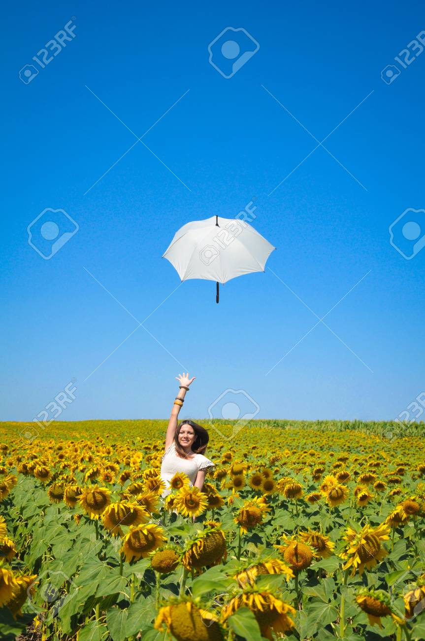 Young woman with umbrella on field in sunflower Stock Photo - 14774993