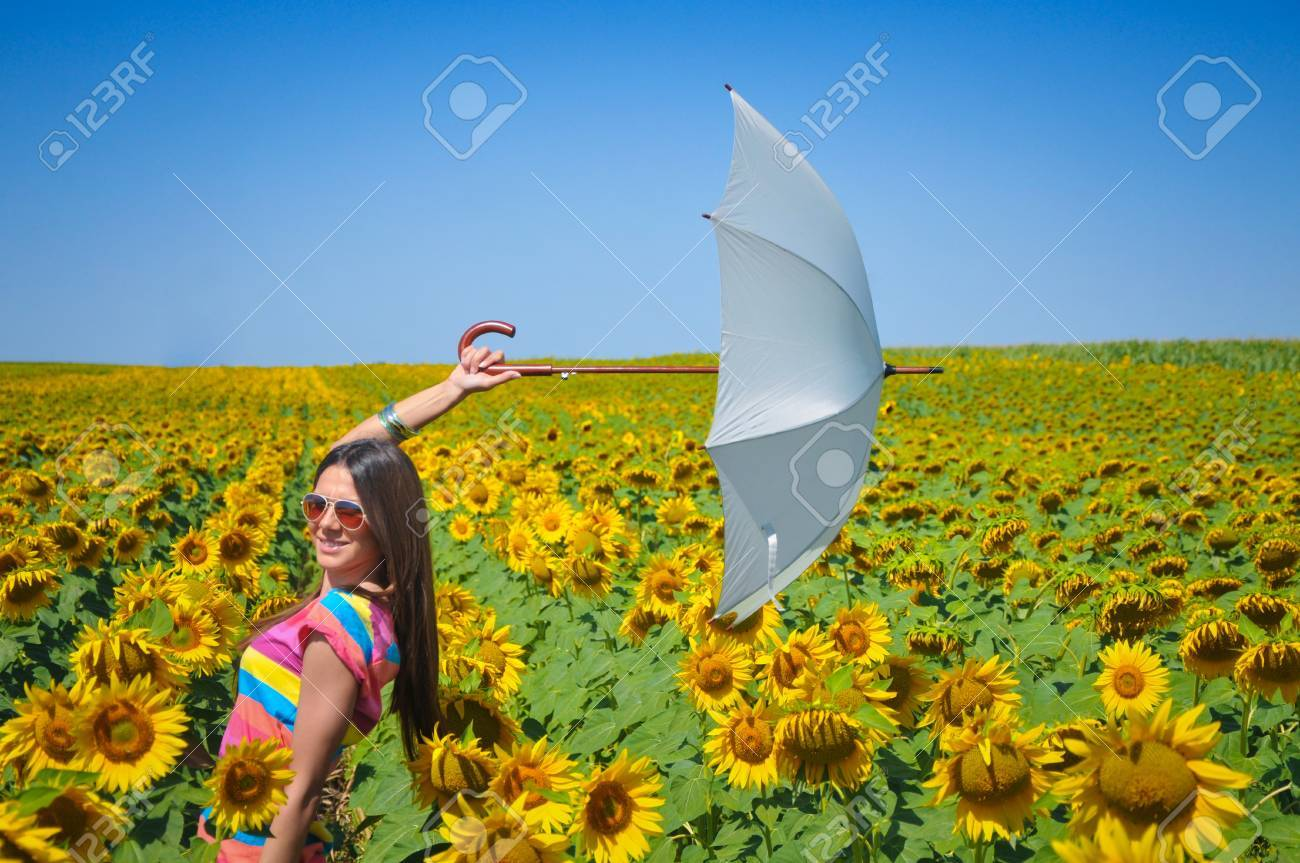 Young woman with umbrella on field in sunflower Stock Photo - 14790272