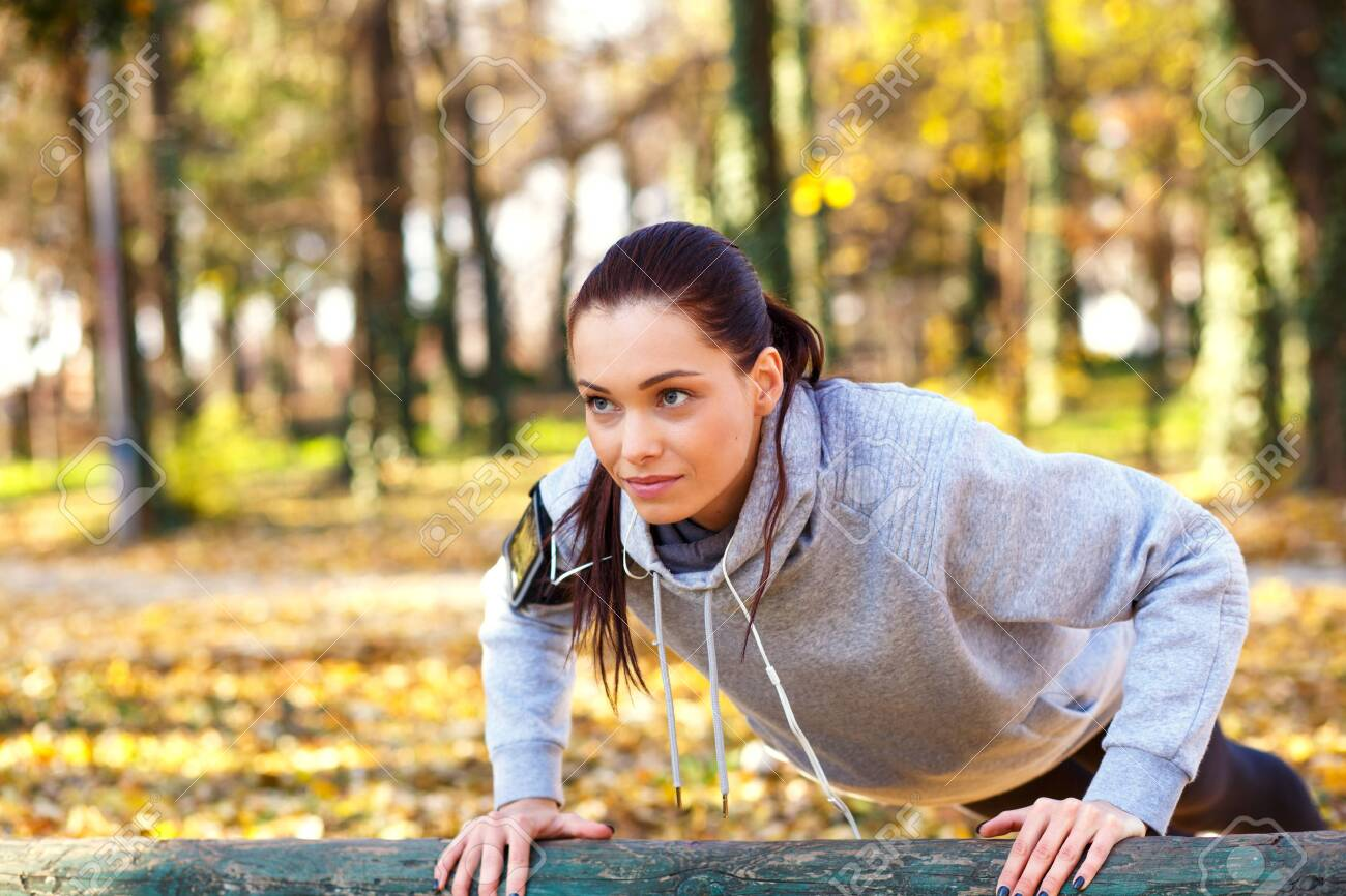 Attractive sporty woman with headphones doing push ups outdoors in the park. - 121561864