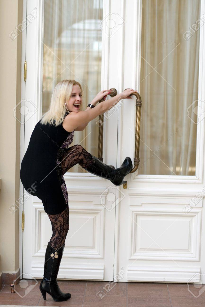 Funny young woman trying to open doors Stock Photo - 7037186