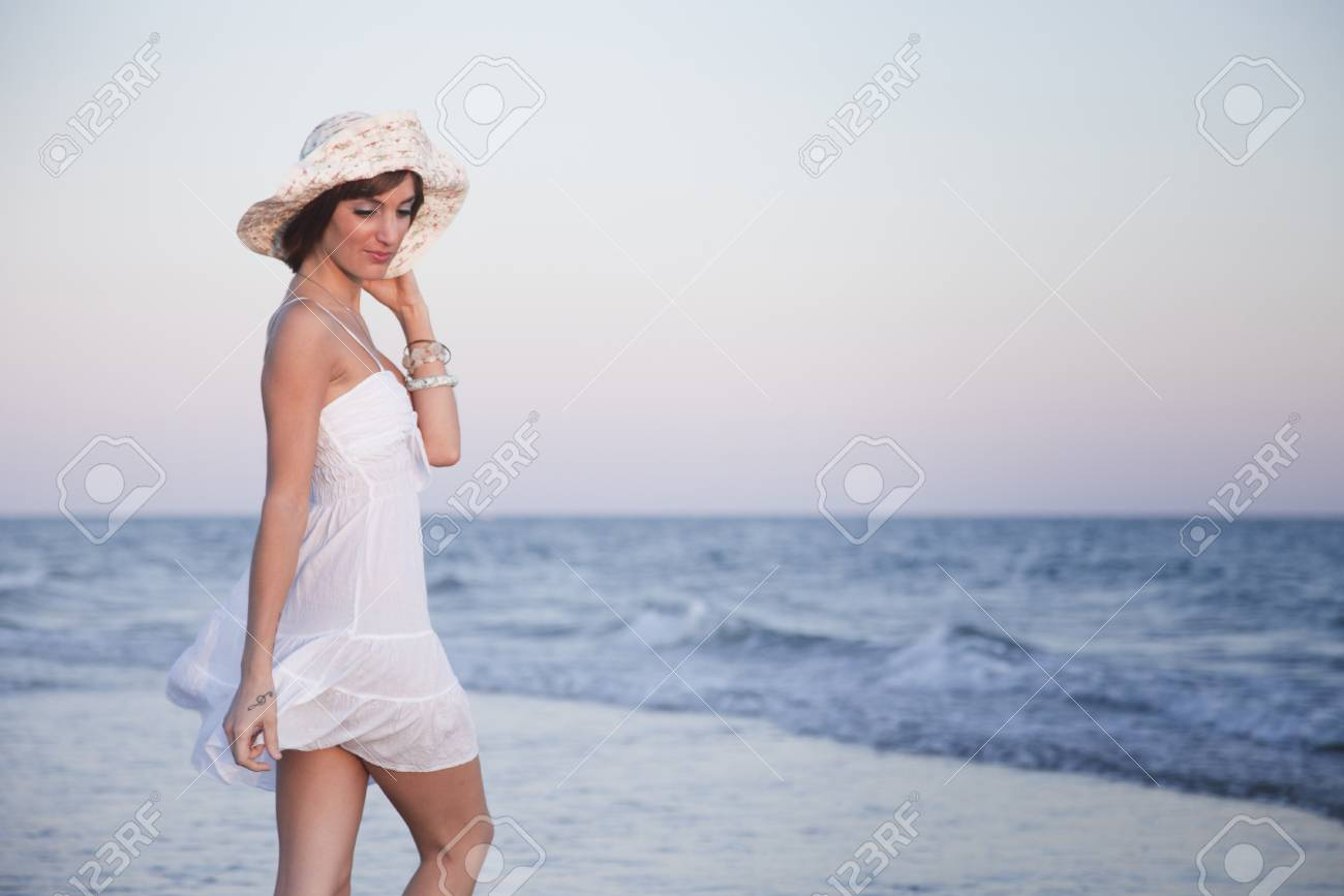 Sexy young girl in a white suit on the beach at sunset Stock Photo - 11155020