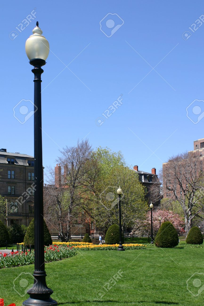 A Lamp Post Stands Tall Over The Boston Public Gardens Surrounded By Old  Brownstone Buildings.