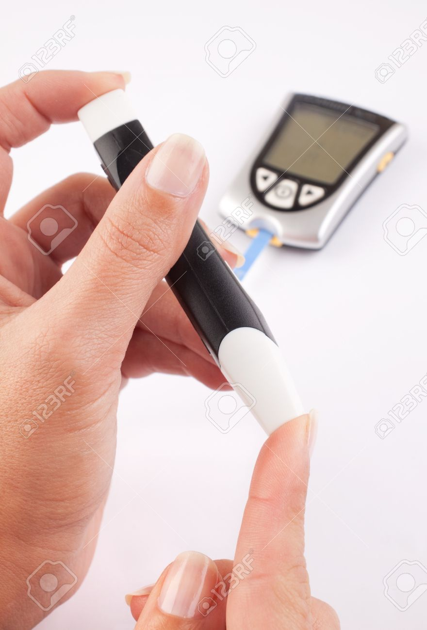 Diabetic woman pricking her finger for a blood test with a glucometer in the background Stock Photo - 7519838