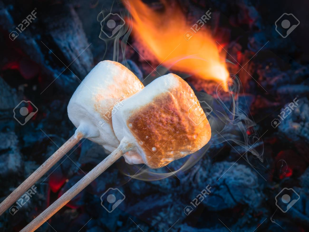 two brown sweet marshmallows roasting over fire flames marshmallow