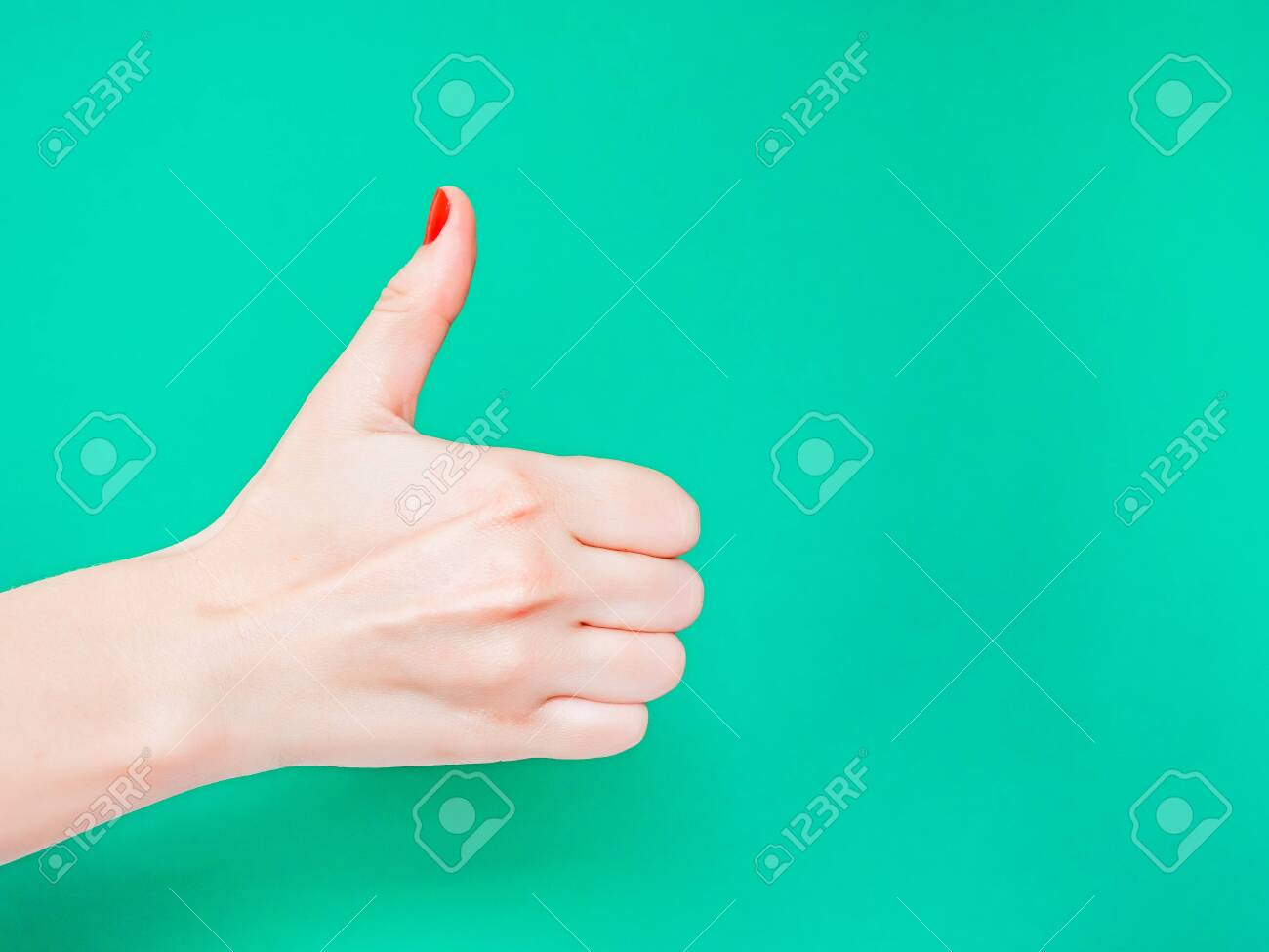 The Thumbs Up Sign. Like Hand Sign. Used when you want to demonstrate that you like something or that you approve of something, The ol thumbs up hand sign. Female hand with red manicure on fingernails holding hand in gesture of likeness giving thumb up on isolated turquoise green color background - 121638490