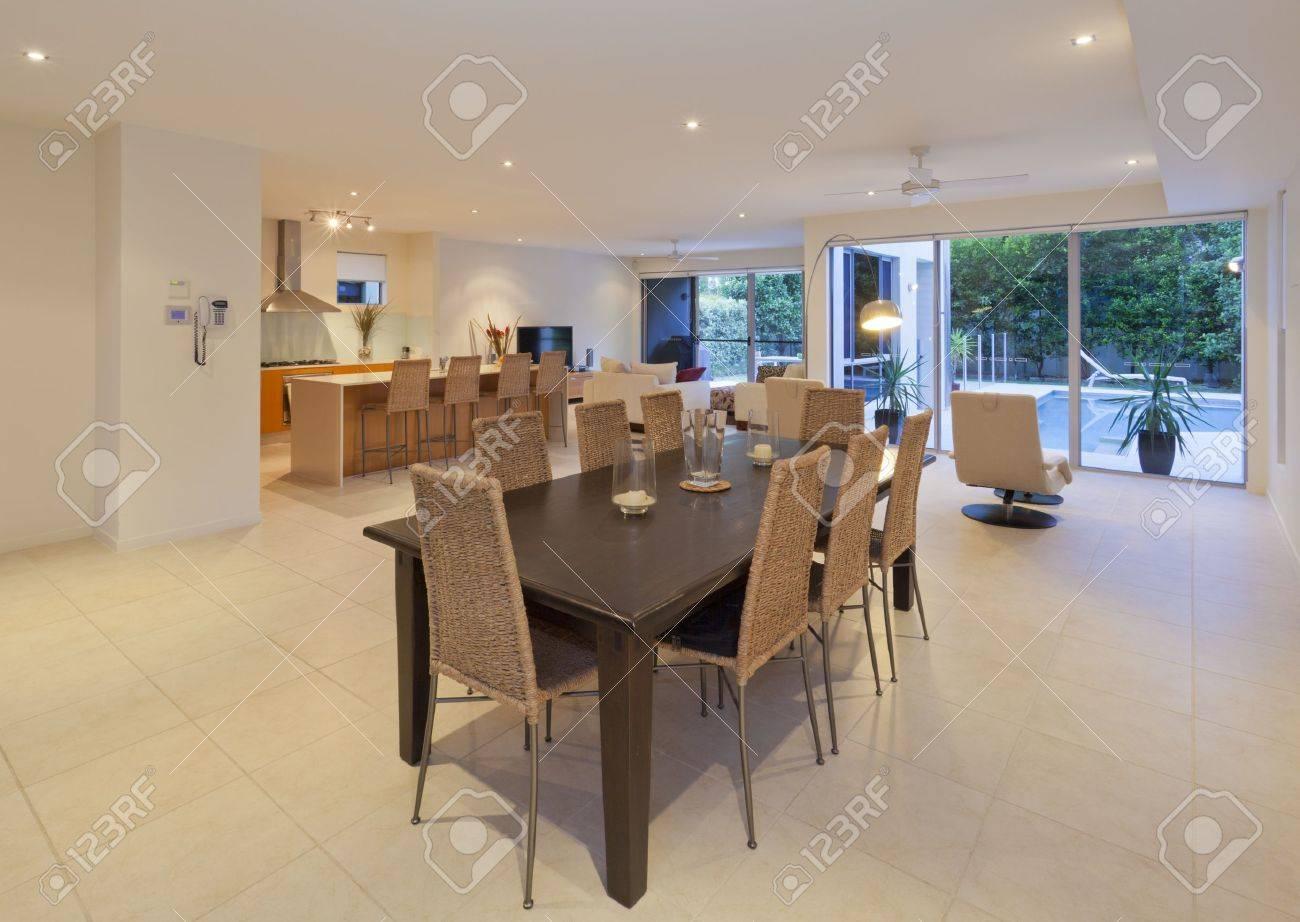 Mesa de comedor de madera y cocina en una casa moderna con vistas al jardín  y piscina