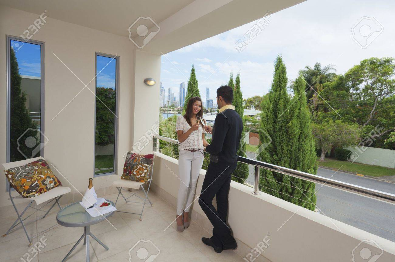 Young couple toasting with champagne on a modern balcony overlooking the city Stock Photo - 12534514