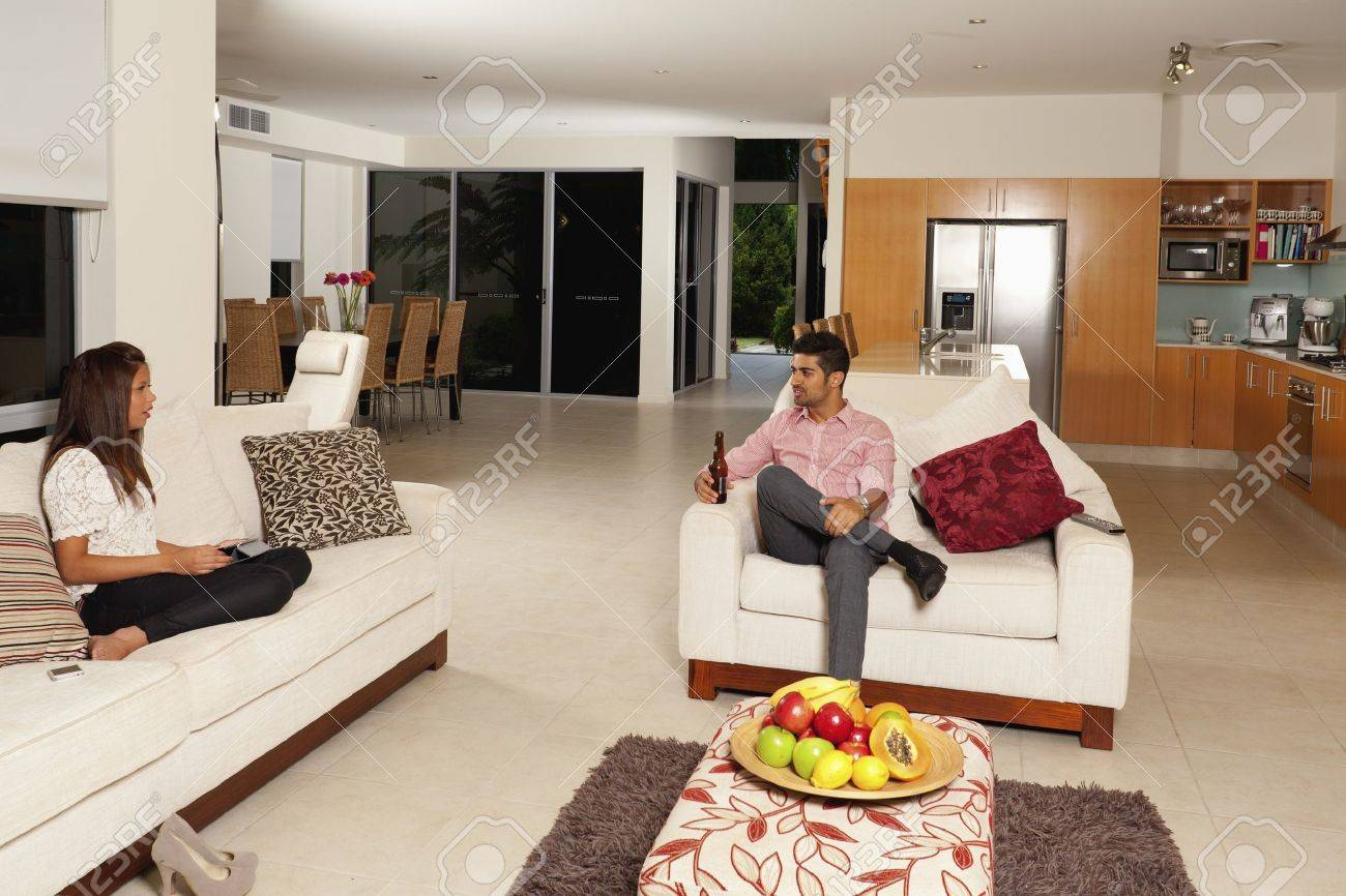 Living Room Decorating Ideas For Young Couples young couple relaxing in modern living room stock photo, picture