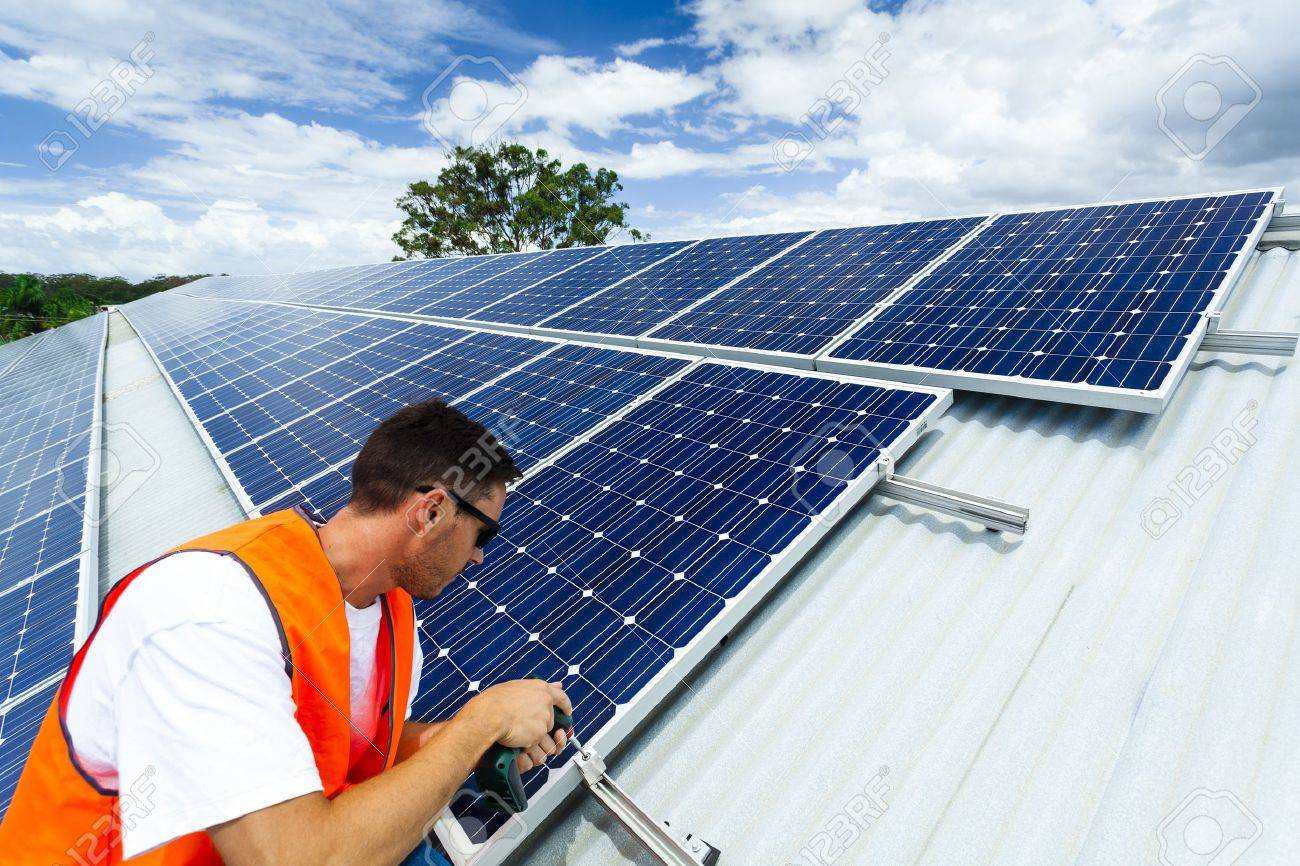 Young Technician Installing Solar Panels On Factory Roof Stock Photo    18445797