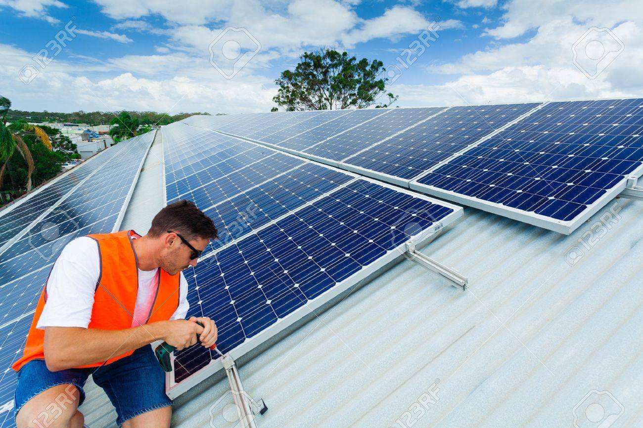 Young technician installing solar panels on factory roof Stock Photo - 18445823