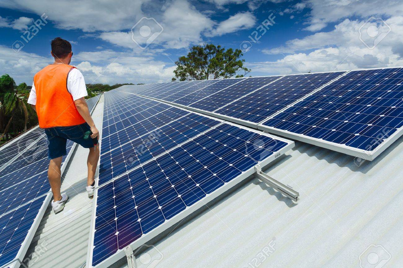 Young technician inspecting solar panels on factory roof Standard-Bild - 18435873