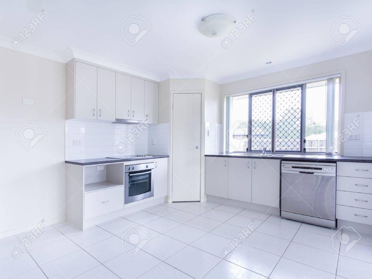 Lege betegelde keuken met afwasmachine roestvrij stalen apparatuur ...