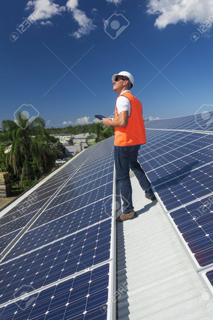 Young technician installing solar panels on factory roof Stock Photo - 19378349
