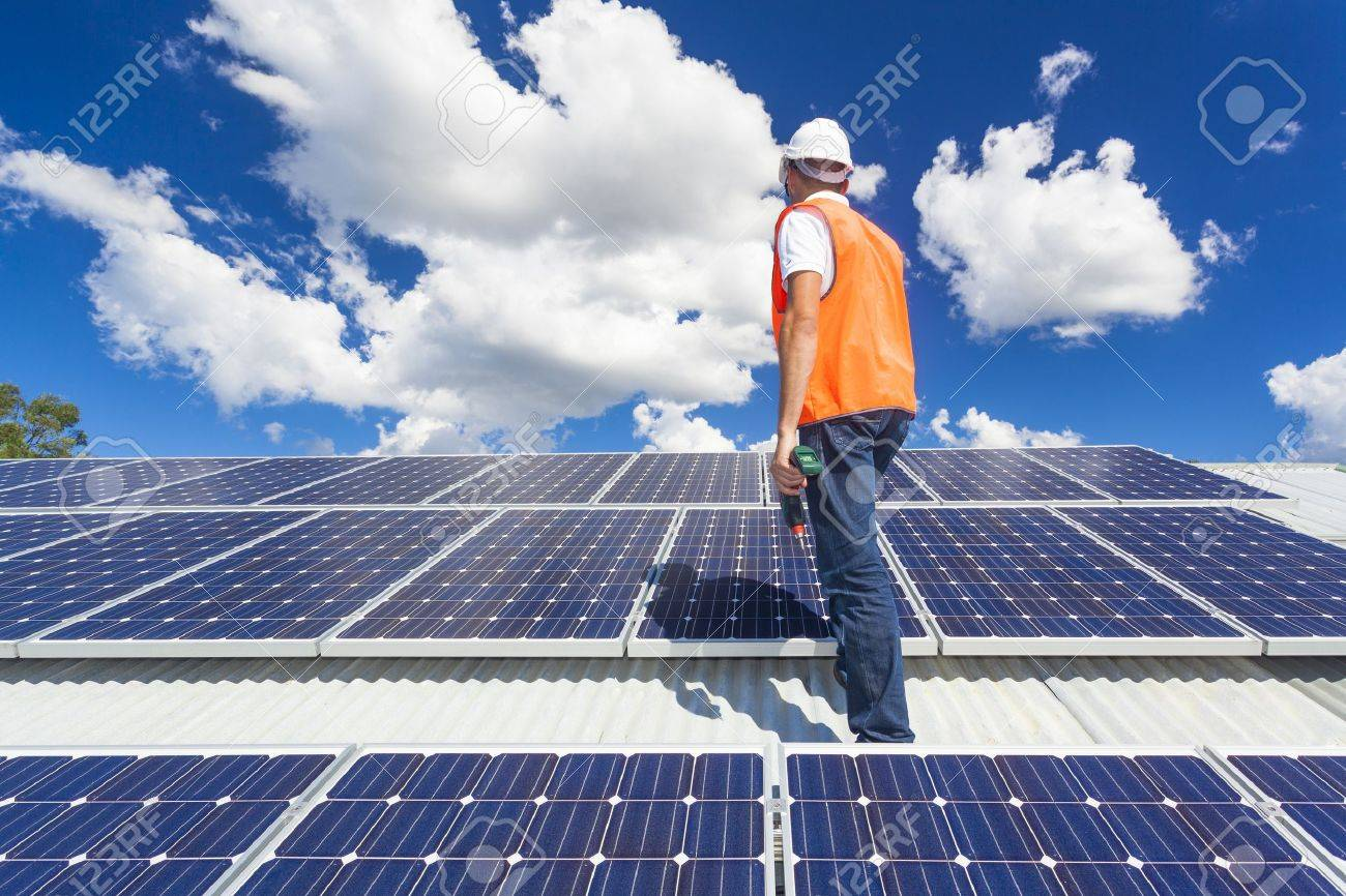 Young technician checking solar panels on factory roof Stock Photo - 21361836