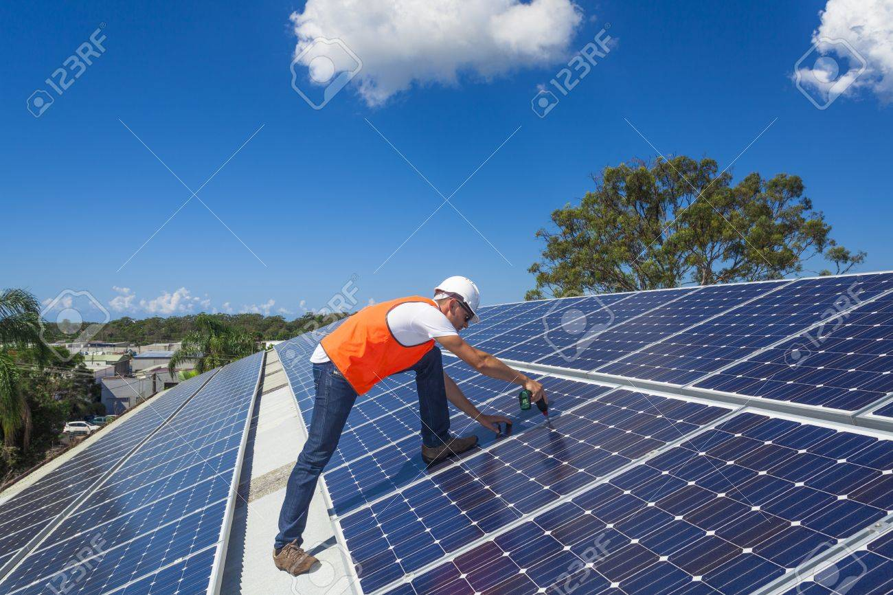 Young Technician Installing Solar Panels On Factory Roof Stock Photo ...
