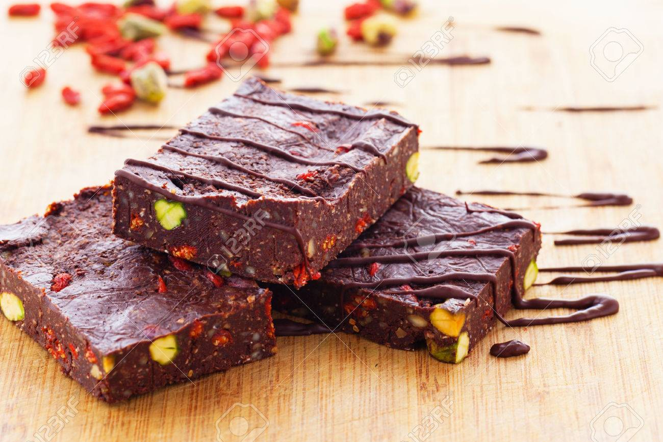 Spicy raw vegan brownies with pistachios and goji berries Standard-Bild - 34434683