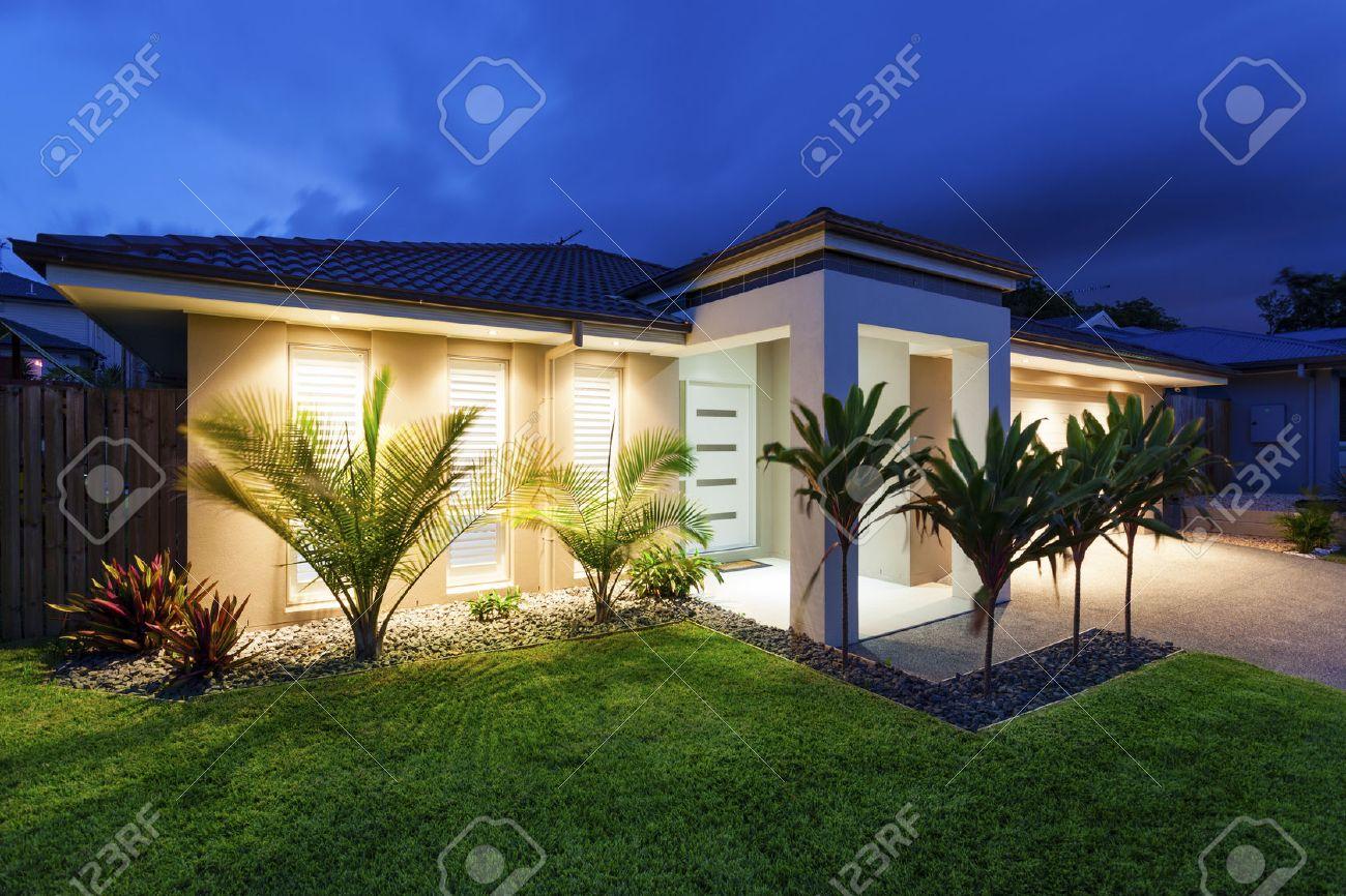 Well lit modern home exterior at dusk Standard-Bild - 37827819