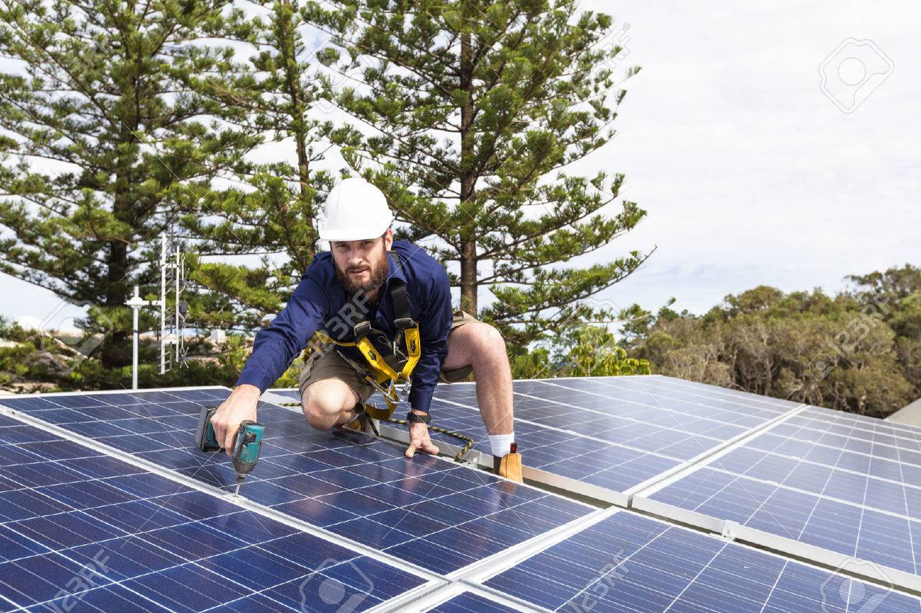 Solar panel technician with drill installing solar panels on roof Standard-Bild - 49589583