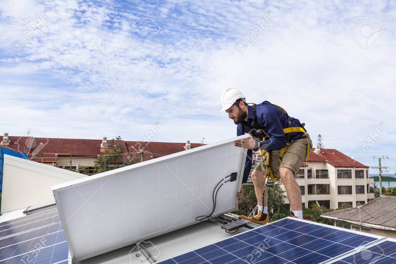 Solar panel technician checking solar panel installation on roof Standard-Bild - 49589593