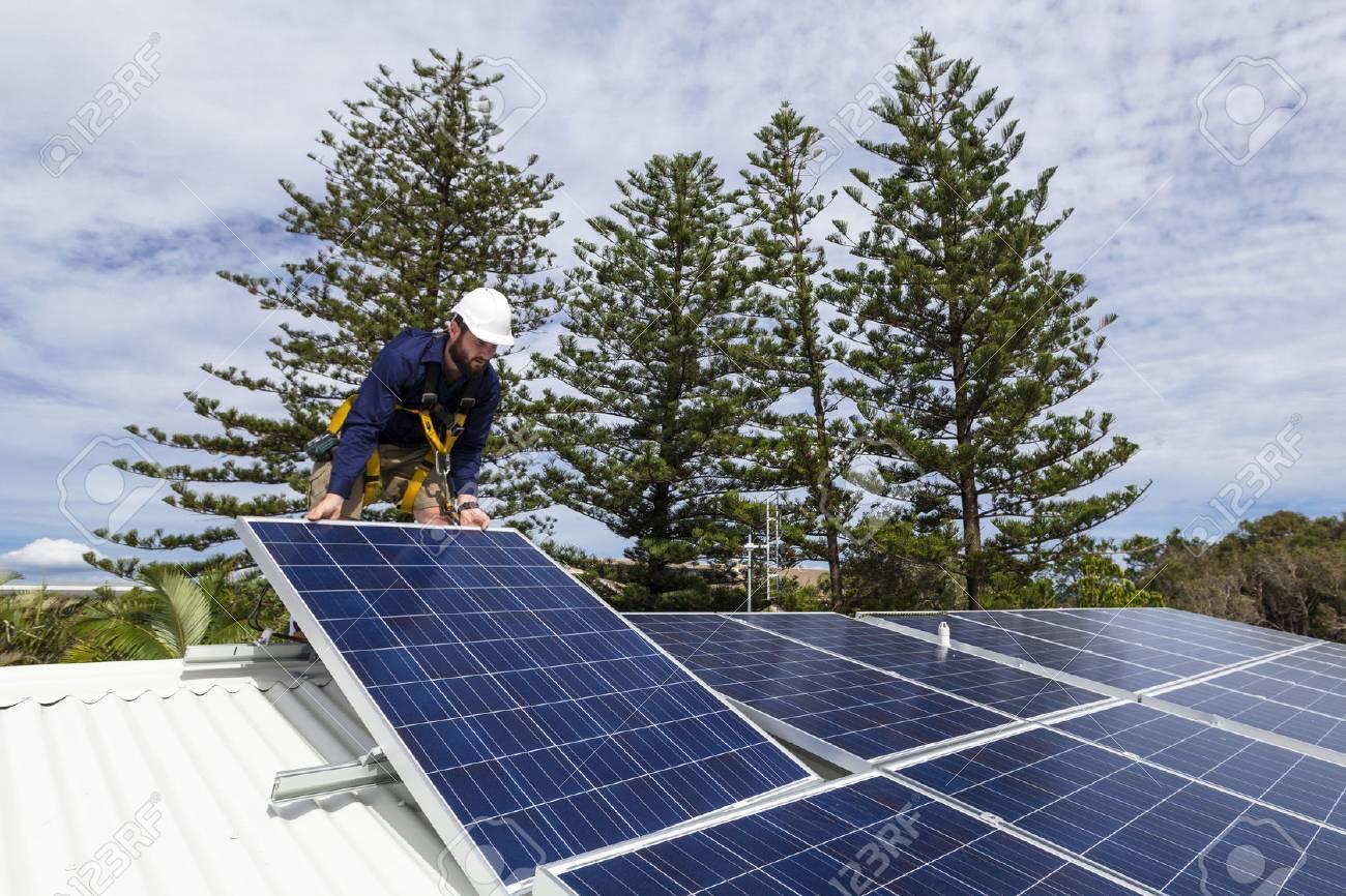 Solar panel technician installing solar panels on roof Standard-Bild - 49589594