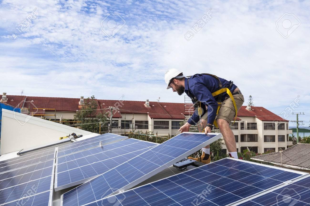 Solar panel technician installing solar panels on roof Standard-Bild - 49589596