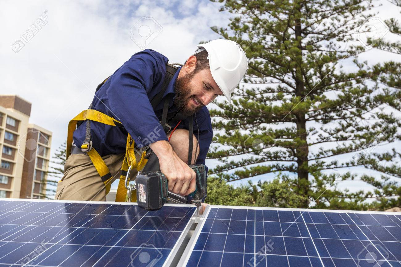 Solar panel technician with drill installing solar panels on roof Standard-Bild - 49589601