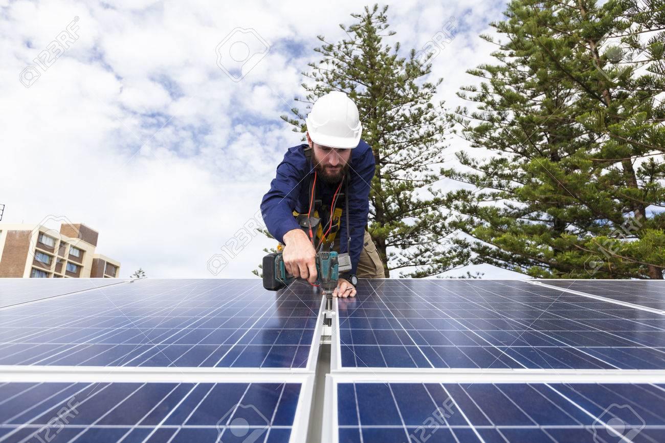 Solar panel technician with drill installing solar panels on roof Standard-Bild - 49589603