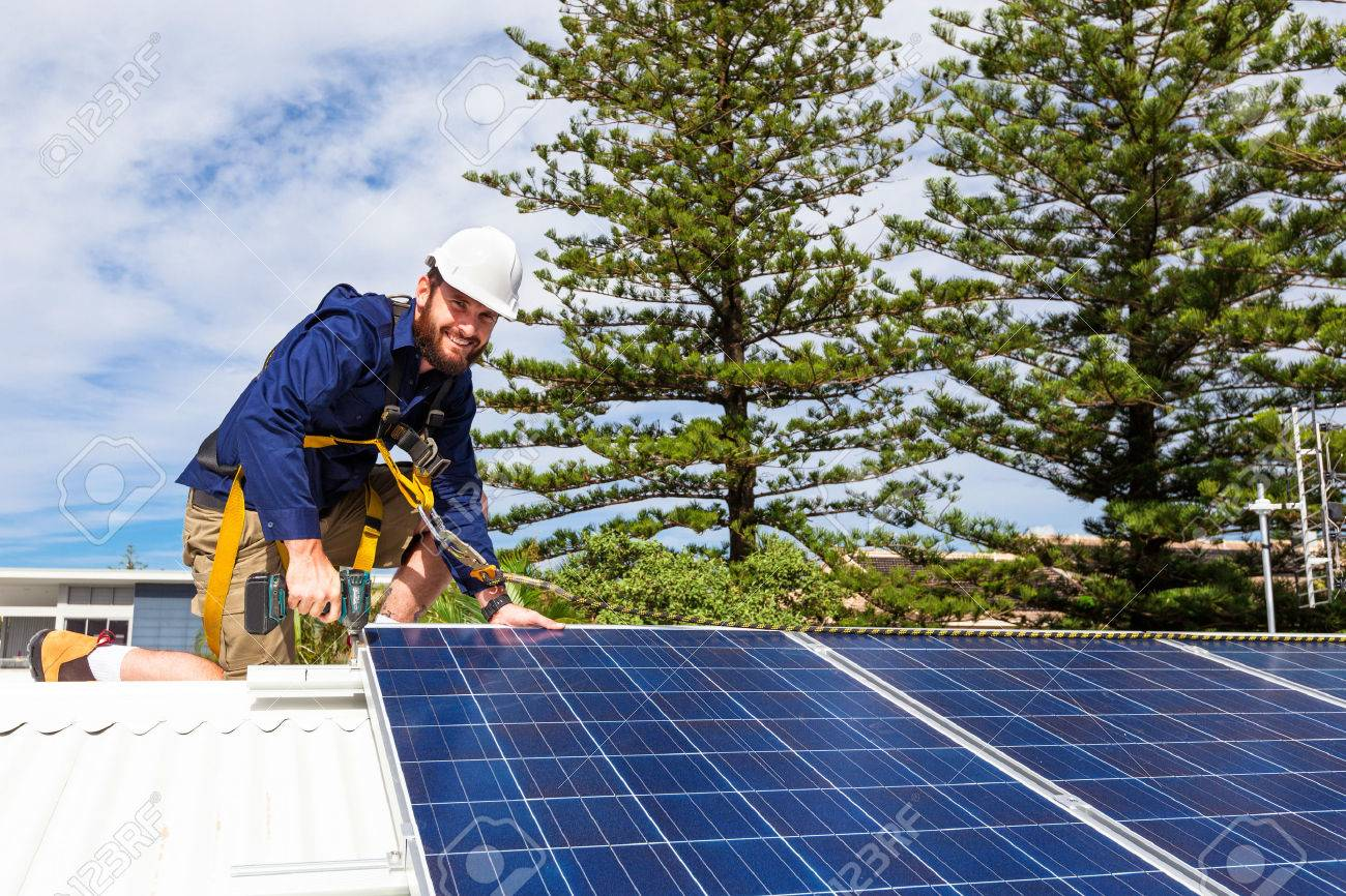 Solar panel technician with drill installing solar panels on roof Standard-Bild - 49589694