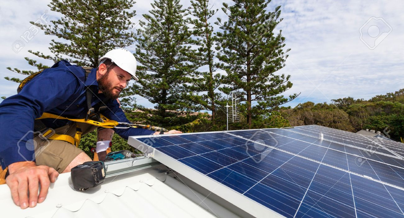 Solar Panel Technician With Drill Installing Solar Panels On Roof Photo
